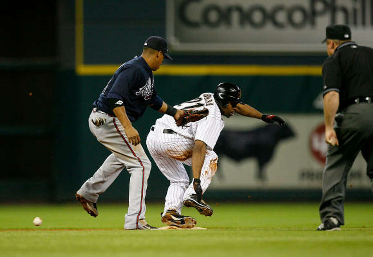 Houston's Michael Bourn (center) slides safely after stealing second base as Atlanta's Yunel Escobar (left) applies a tag without the ball in the fourth inning.