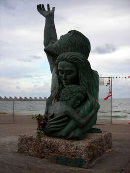 """The 1900 Storm statue has also become home to Ike """"offerings."""" Here, someone left some flowers as well as a painted wooden plank at the bottom of the statue in remembrance of Gulf Coast storms. Photo: ROBERT STANTON, HOUSTON CHRONICLE"""