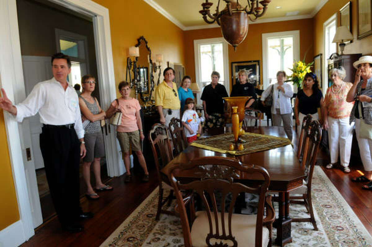Hal Williams, left, gives a tour of the dining room of the home on Avenue K.