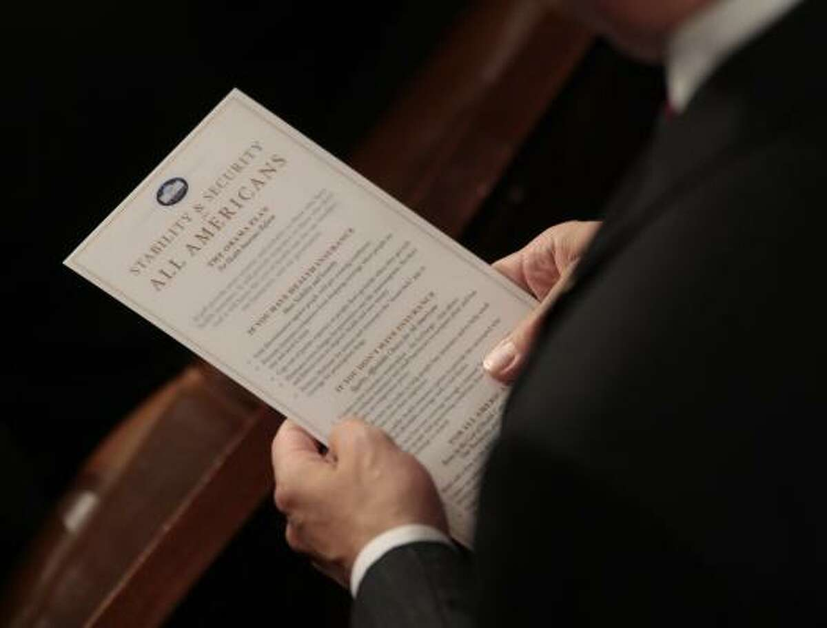 A member of Congress reads Obama's health care plan on Capitol Hill.