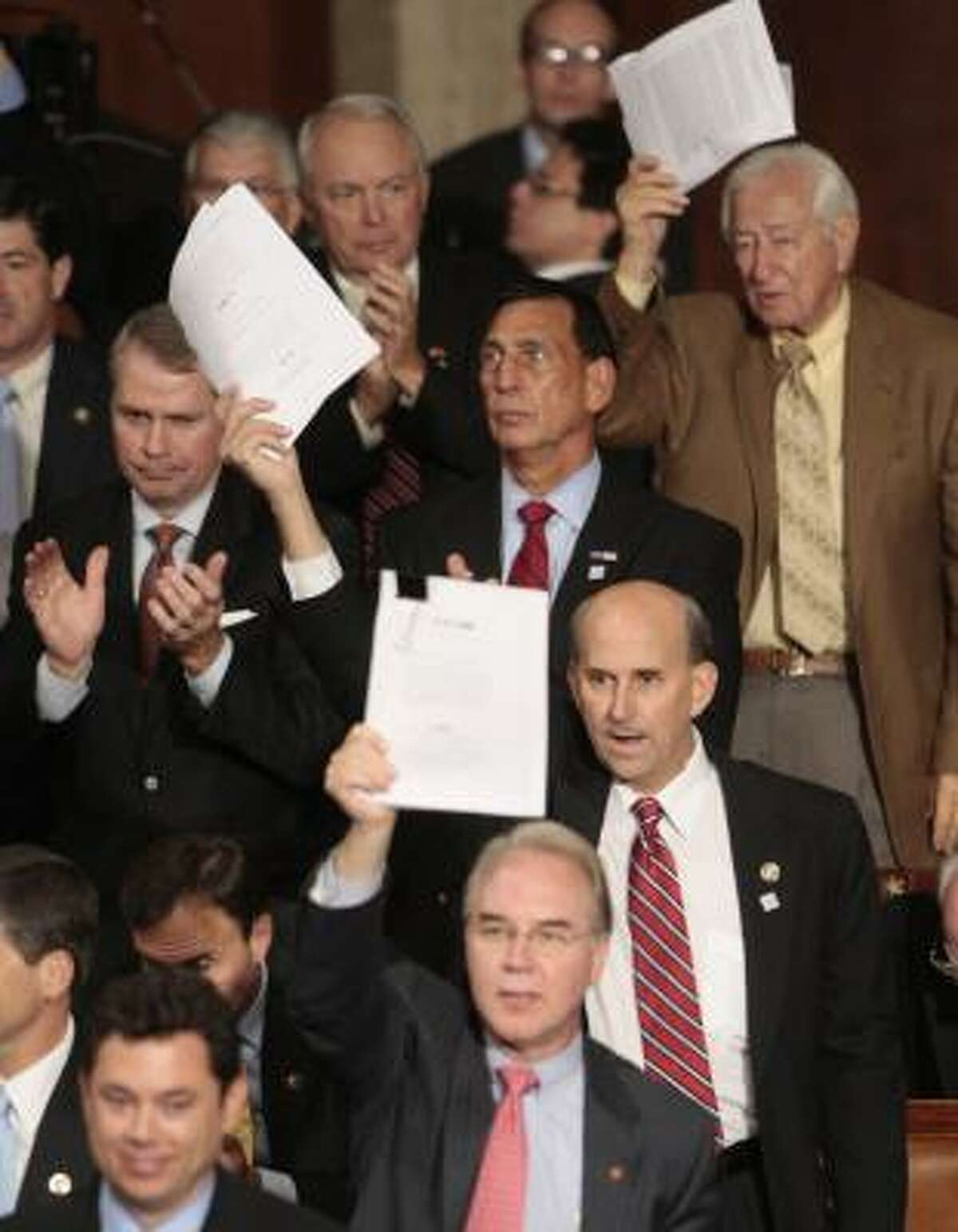 Republican House members wave copies of their health care bill as Obama delivers his speech.