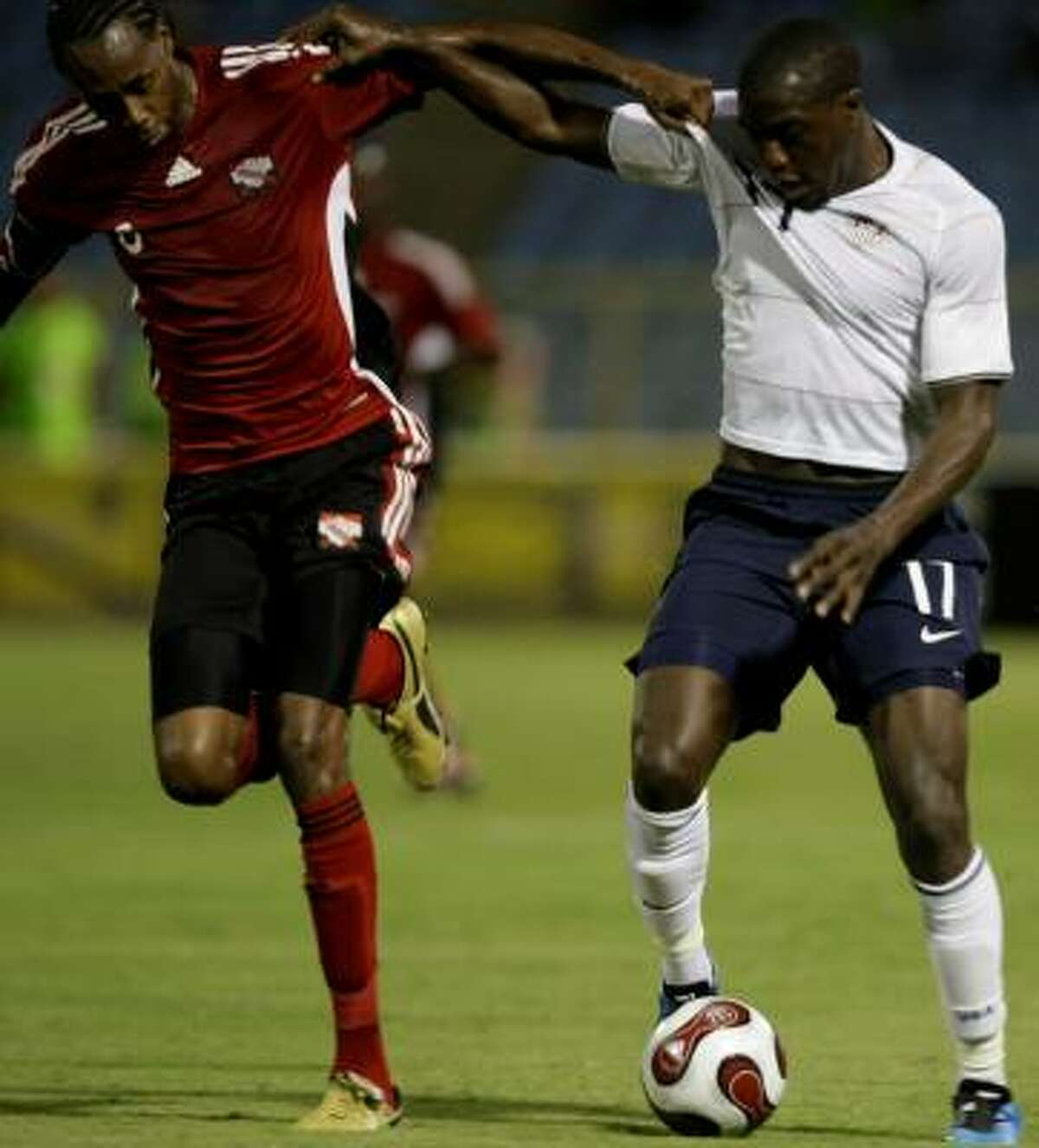 The united States' Jozy Altidore, right, fights for the ball with Trinidad and Tobago's Dennis Lawrence.