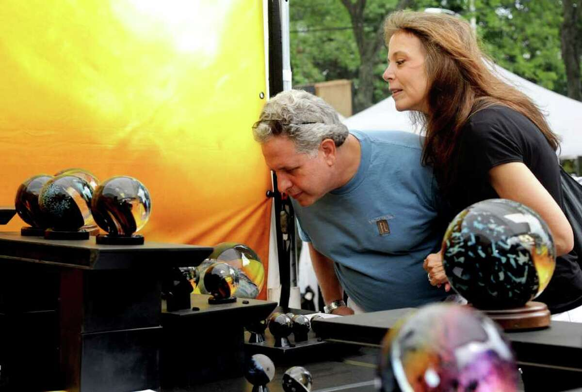 Tracy Gilman and Bruce Frank look at internal fire glass by Scott Pernicka at the 35th annual SoNo Arts Celebration in South Norwalk on Saturday, August 6, 2011.