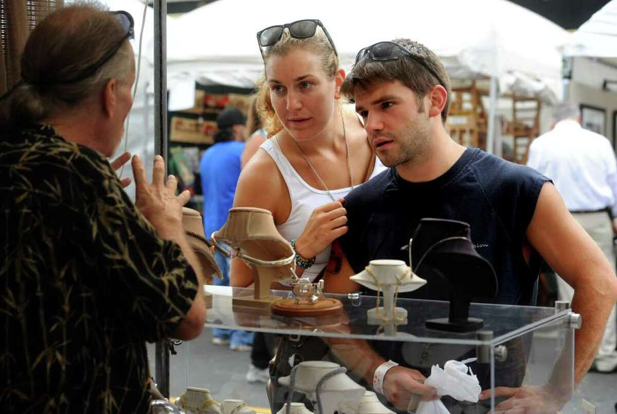 Shoana Van Wyngaarden and Garret Mitchell look at jewelry by Mark Van de Bogart at the 35th annual SoNo Arts Celebration in South Norwalk on Saturday, August 6, 2011.