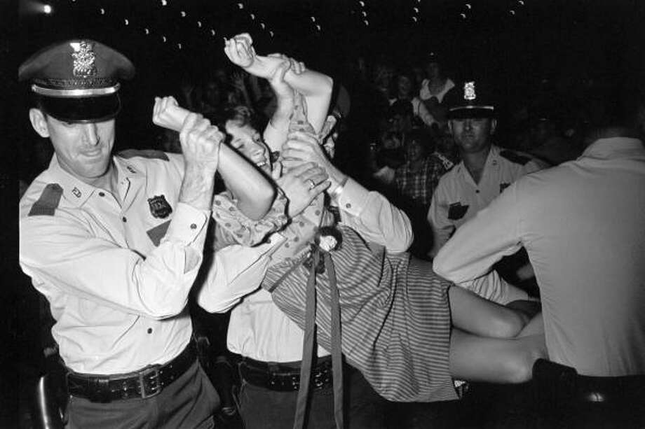A Beatles fan is carried off by police during the Fab Four's performance at the Coliseum in Houston. Photo: Houston Chronicle