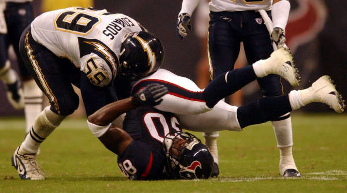 Texans wide receiver Andre Johnson, center, gets turned over after the catch over San Diego Chargers Donald Edwards in the first half of play at Reliant Stadium.