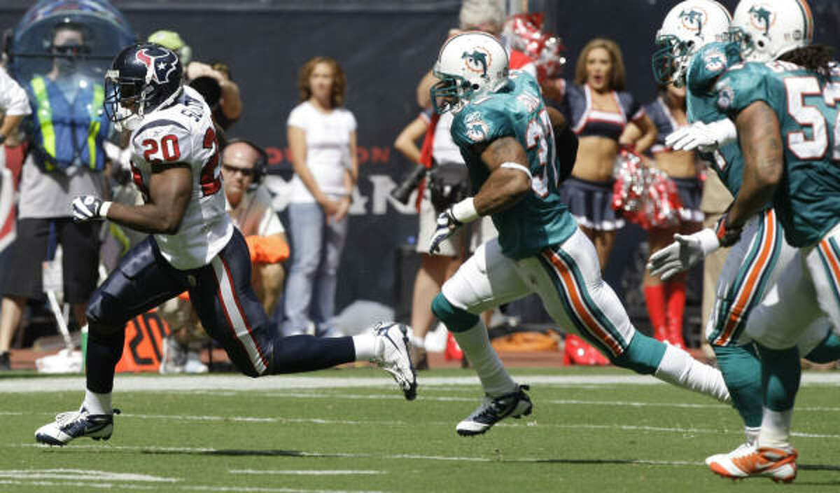 Texans running back Steve Slaton, left, breaks away for a long gain in the first quarter against the Miami Dolphins at Reliant Stadium.