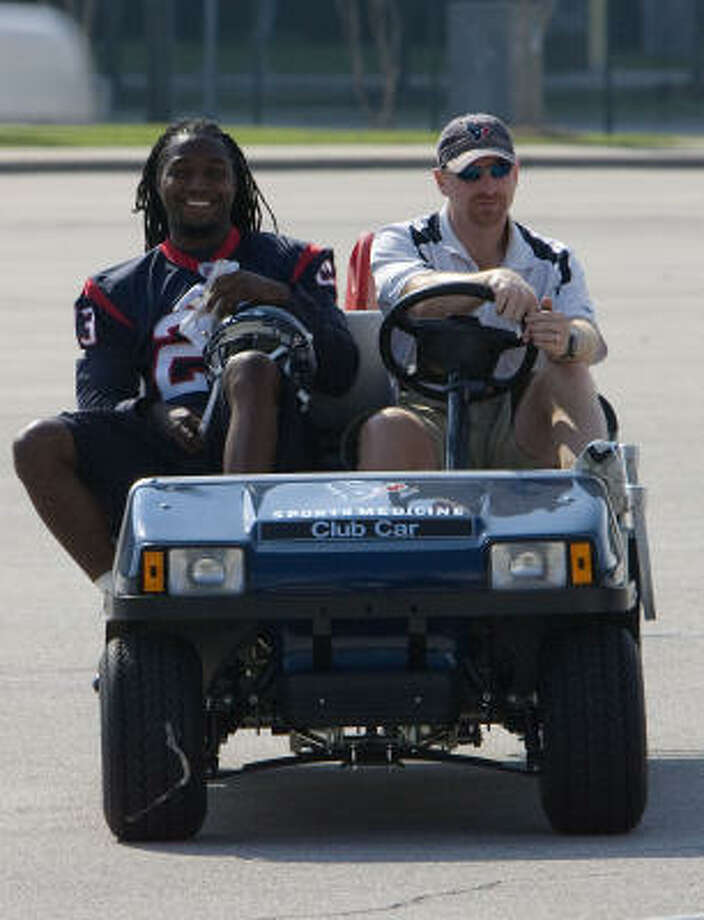 Texans cornerback Dunta Robinson gets a lift to Sunday's practice from head athletic trainer Geoff Kaplan. Photo: James Nielsen, Chronicle