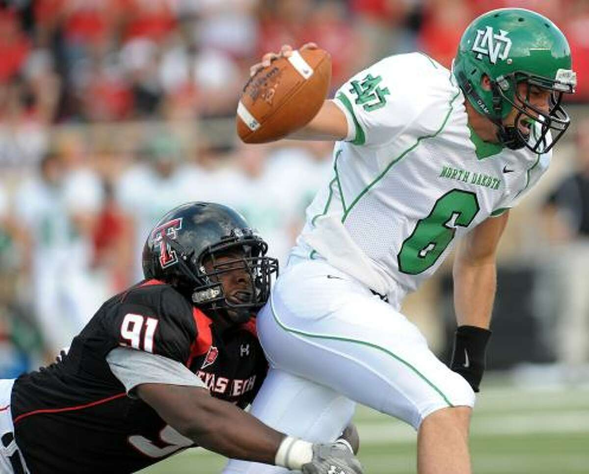 Texas Tech's Rajon Henley, left, brings down North Dakota's Jake Landry, who rushed for 17 yards on eight carries.