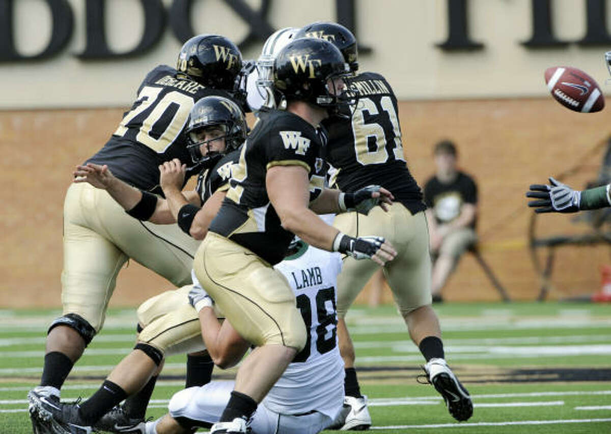 Wake Forest quarterback Riley Skinner avoids being sacked by Baylor defensive tackle Jason Lamb by throwing an incomplete pass during the Bears' 24-21 victory in Winston-Salem, N.C.