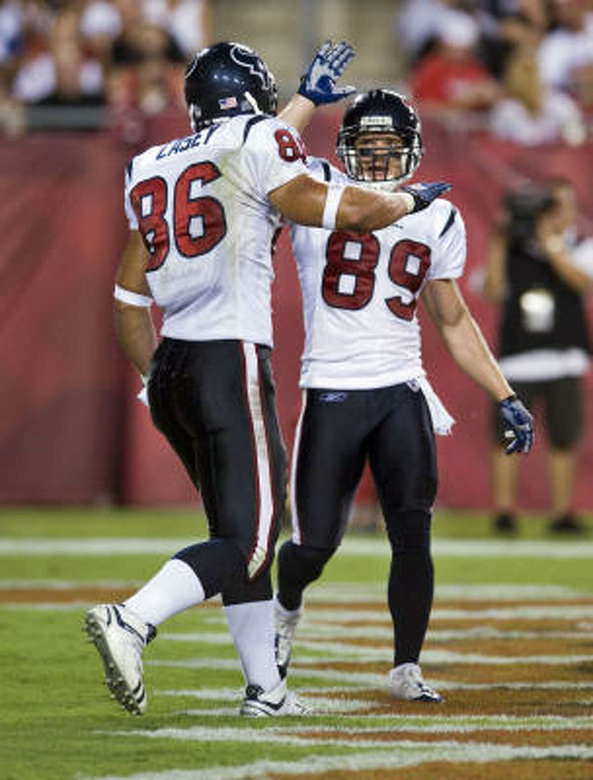The Texans' David Anderson, right, congratulates James Casey after Casey's 11-yard touchdown catch from quarterback Rex Grossman during the second quarter.