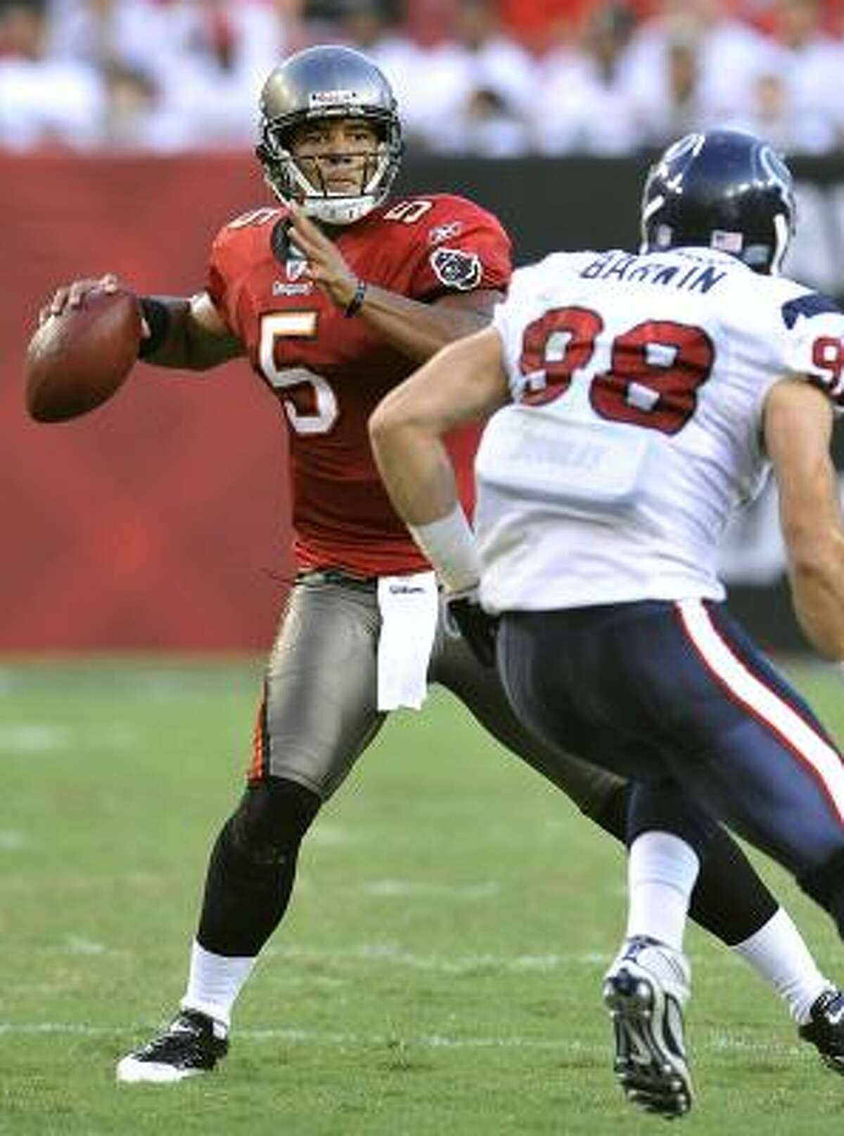 Tampa Bay quarterback Josh Freeman prepares to pass while being chased by Texans defensive end Conner Barwin.