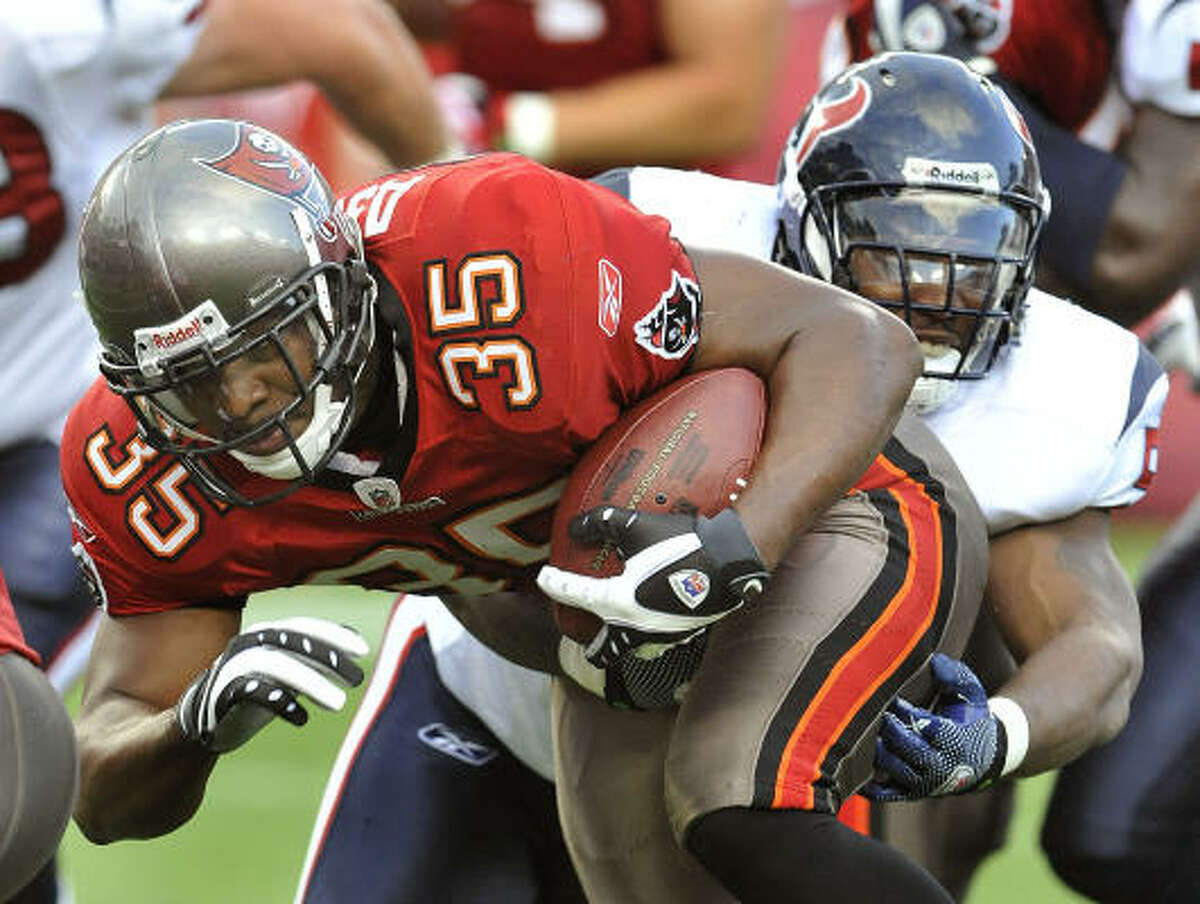 Tampa Bay fullback B.J. Askew is caught from behind by Texans linebacker Kevin Bentley during the first quarter.