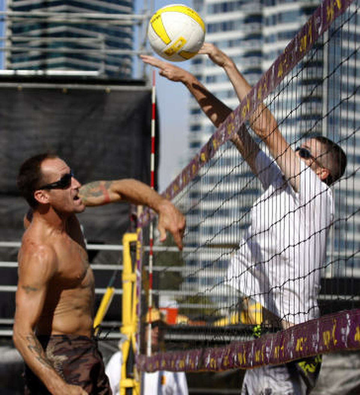 Tim Wooliver (left) slams the ball past Steve Hennings in the first round of the AVPNext Championship Cup.