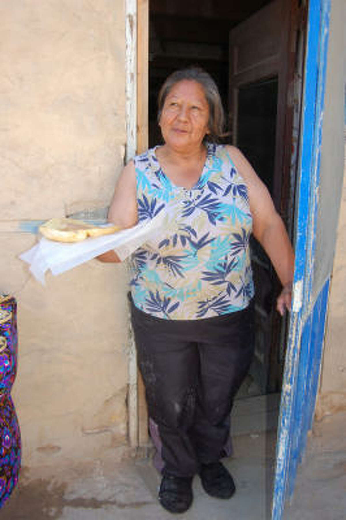 Francesca offers fry bread to visitors from her turquoise screen door in the Acoma Pueblo near Albuquerque, N.M.