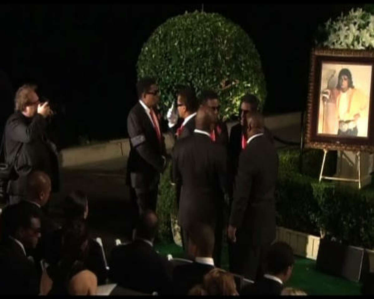 An image from video shows the star's brothers at the burial.