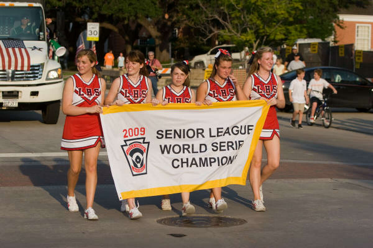 Lamar High School cheerleaders carry the championship banner.