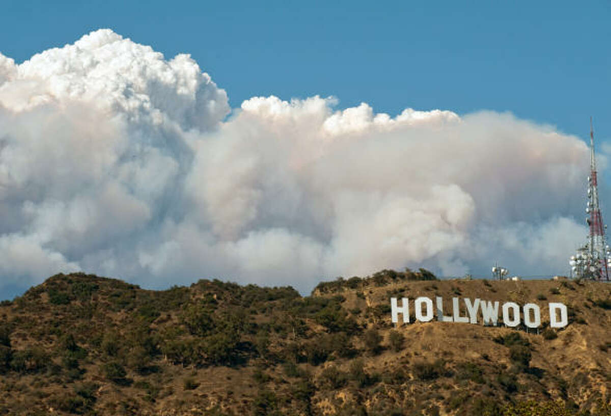 Smoke billows up from behind the Hollywood Hills in Los Angeles. Wildfires threaten 12,000 suburban homes and have been raining ash on cars as far away as downtown Los Angeles. The flames already scorched 164 square miles of brush and threaten more than 12,000 homes.