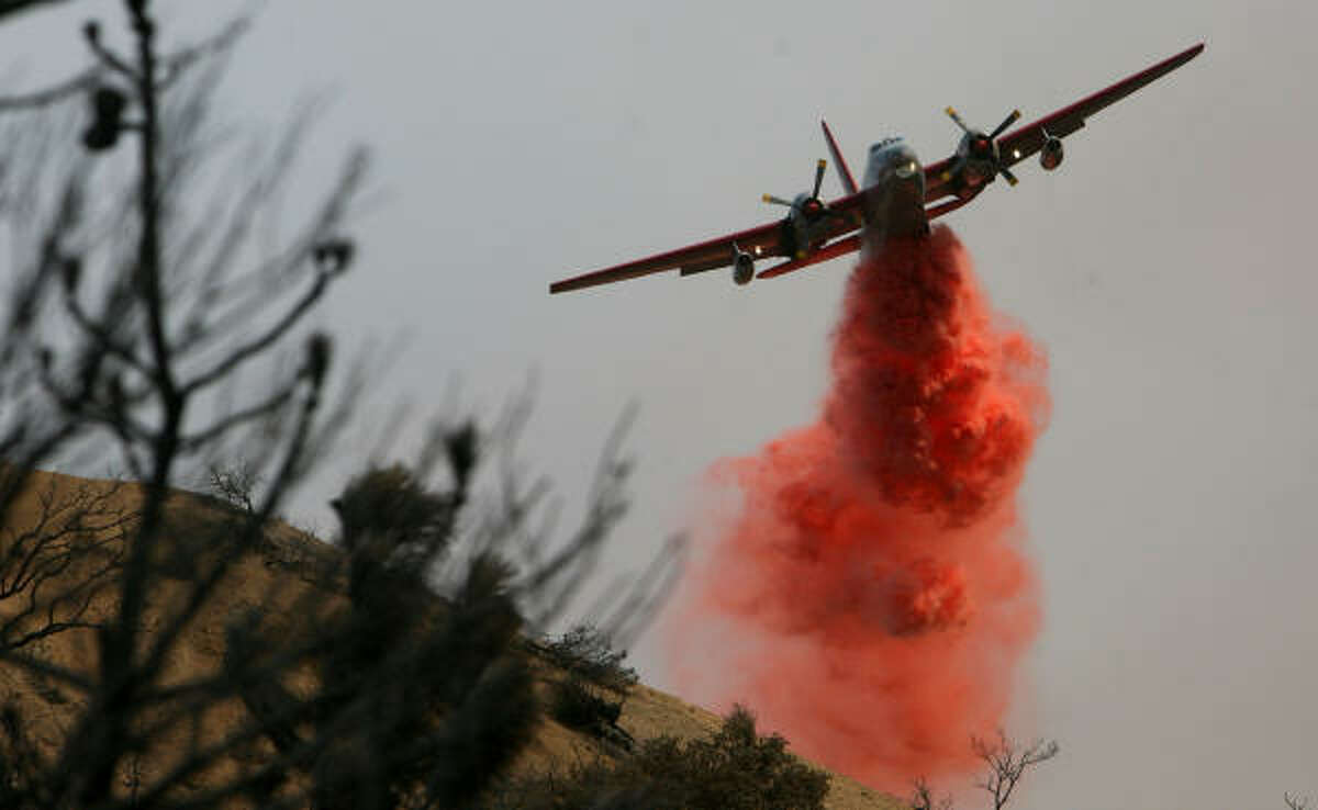 An tanker drops fire retardant on brush in an attempt to control the Station Fire, which has burned more than 85,000 acres and has forced thousands of evacuations.