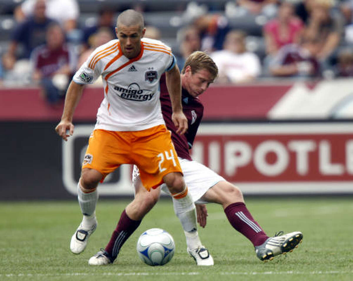 Dynamo defender Wade Barrett, front, works the ball down the field as Colorado Rapids midfielder Jacob Peterson defends.