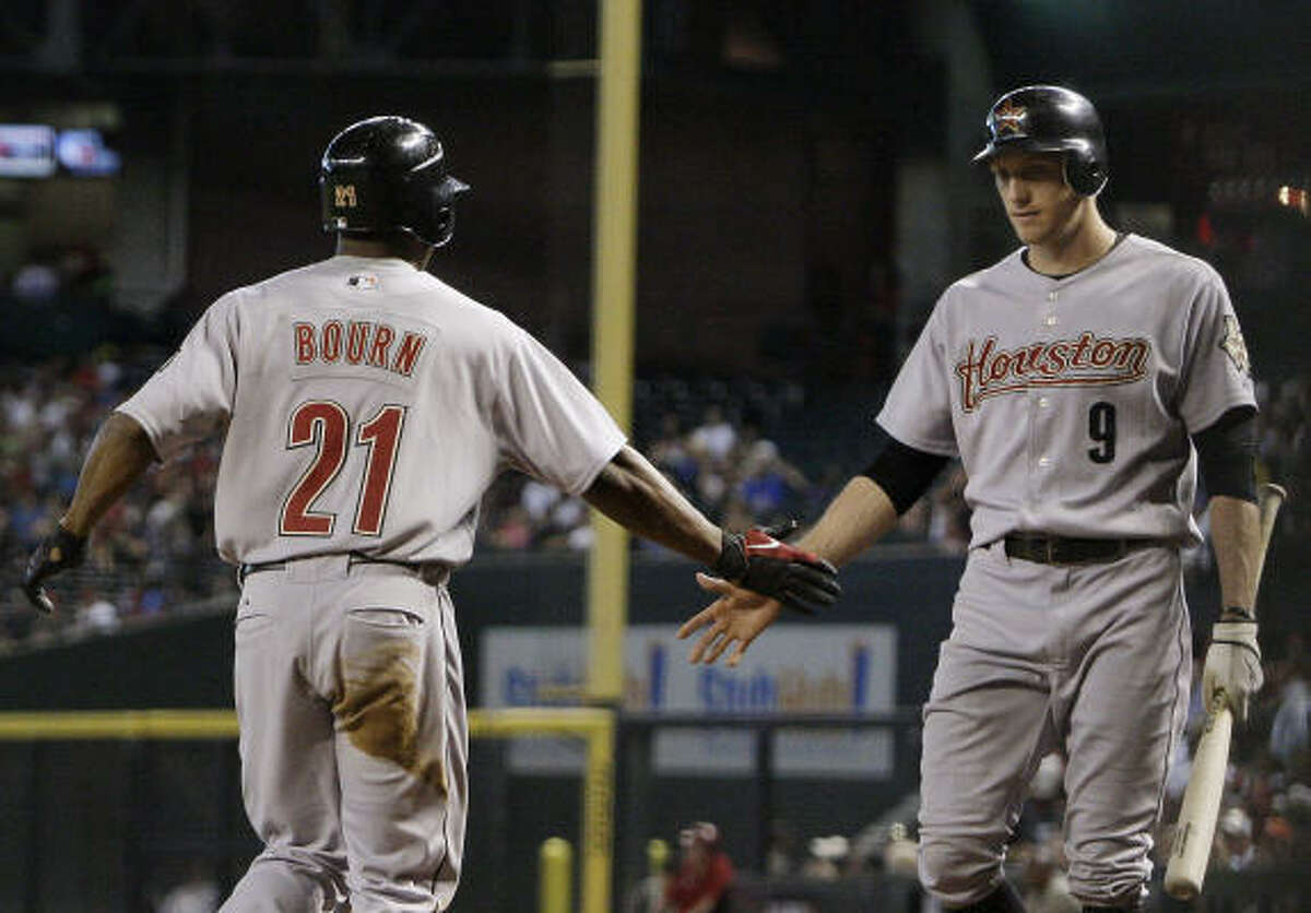 Astros' Michael Bourn celebrates the run he scored with teammate Hunter Pence in the first inning.