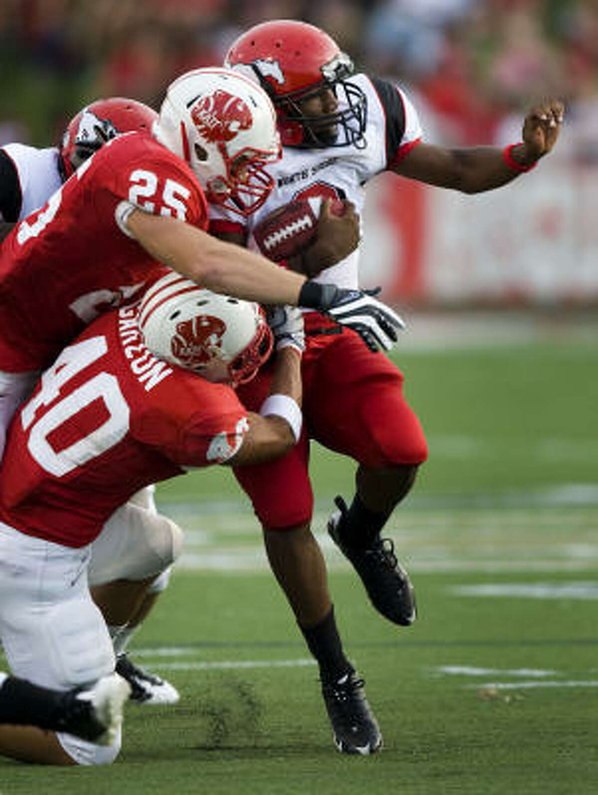 North Shore's Devon Gibson (right) is brought down by Katy's Sam Holl (25) and Andrew Garzon (40) during the first half.