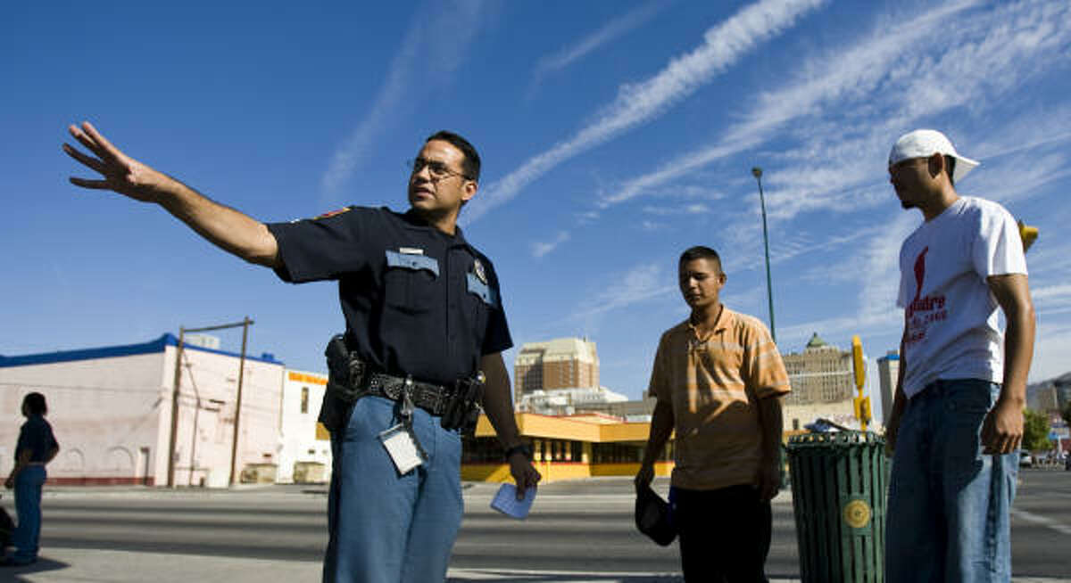 El Paso Police Department Officer Abel Saenz tells day workers not to trespass on private property Wednesday, Aug. 12, 2009, in El Paso. Saenz says because El Paso's proximity to Mexico, the police and the community need to be vigilant when it comes to reporting crime.