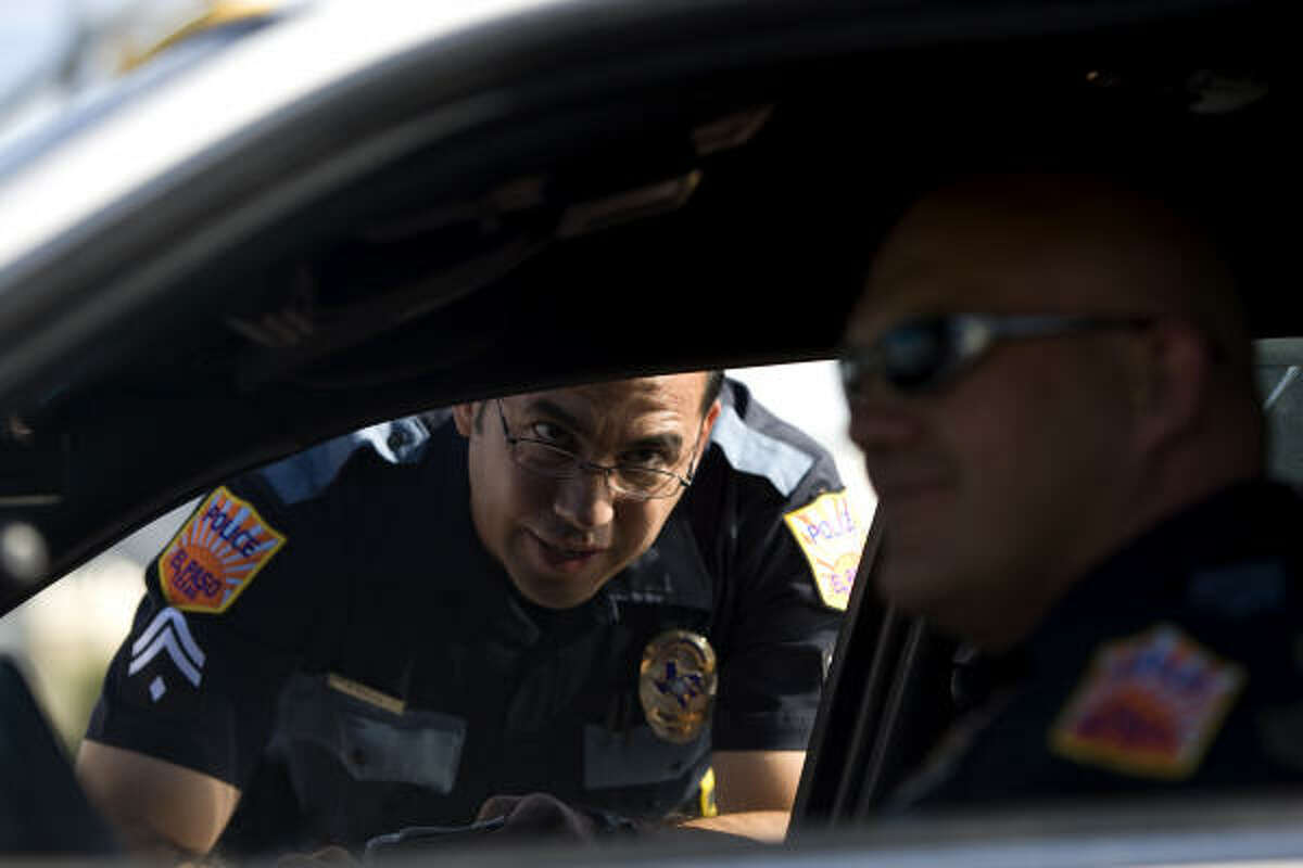 El Paso Police Officer Abel Saenz, left, briefs his supervisor Sgt. Jeffrey Wall about a call involving several people and a business Wednesday, Aug. 12, 2009, in downtown El Paso. Saenz says that if the police answer calls, people will be more proactive to make calls.