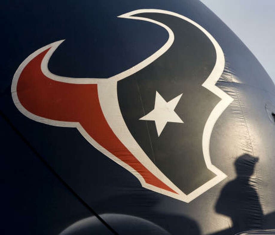 A fan casts a shadow on an giant Texans helmet during a training camp workout Thursday, Aug. 6, 2009. Photo: Brett Coomer, Chronicle