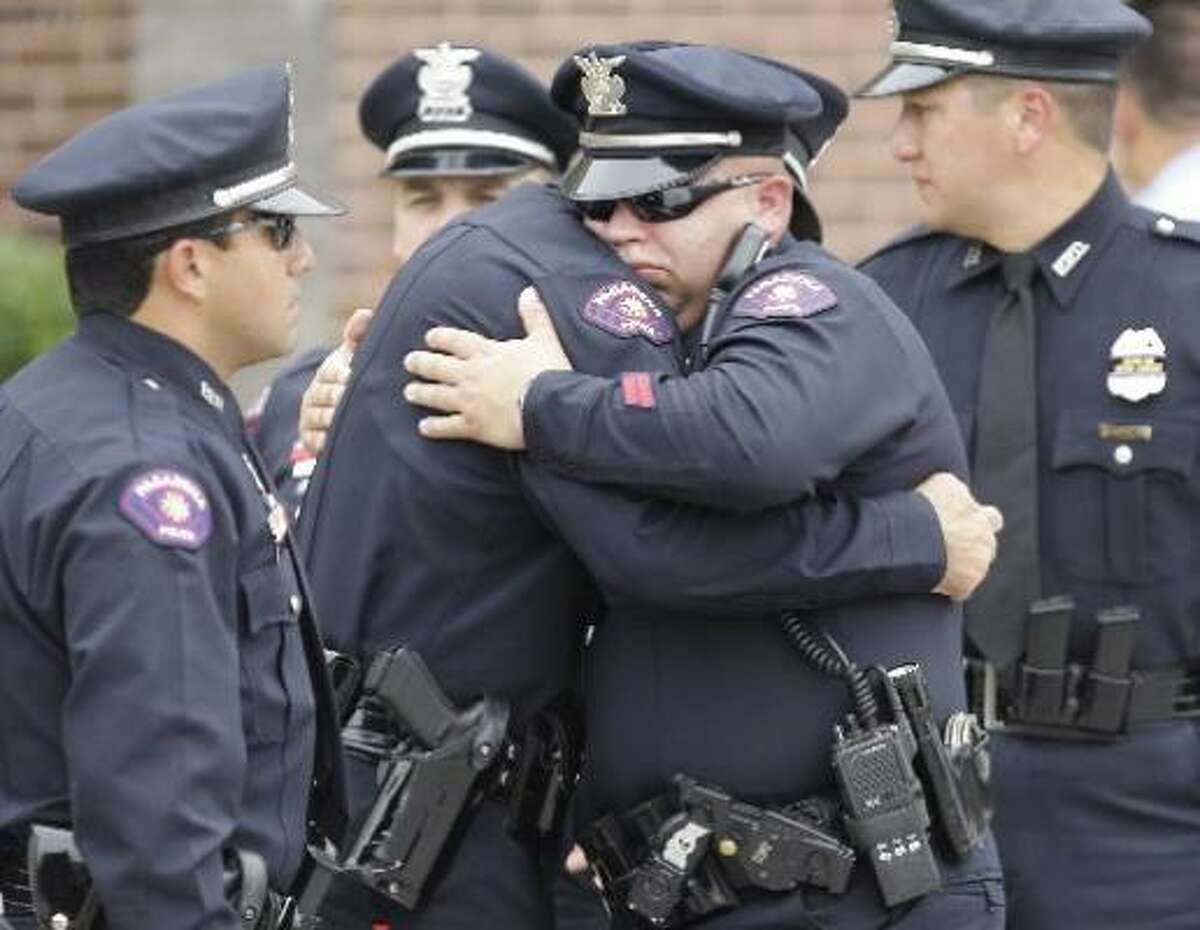 Pasadena Police officers Chad Cook, center left, is hugged by S.T. Wilchek, after funeral service for fellow officer Jesse Hamilton, 29, at Grace Community Church, 14505 Gulf Freeway in Houston.