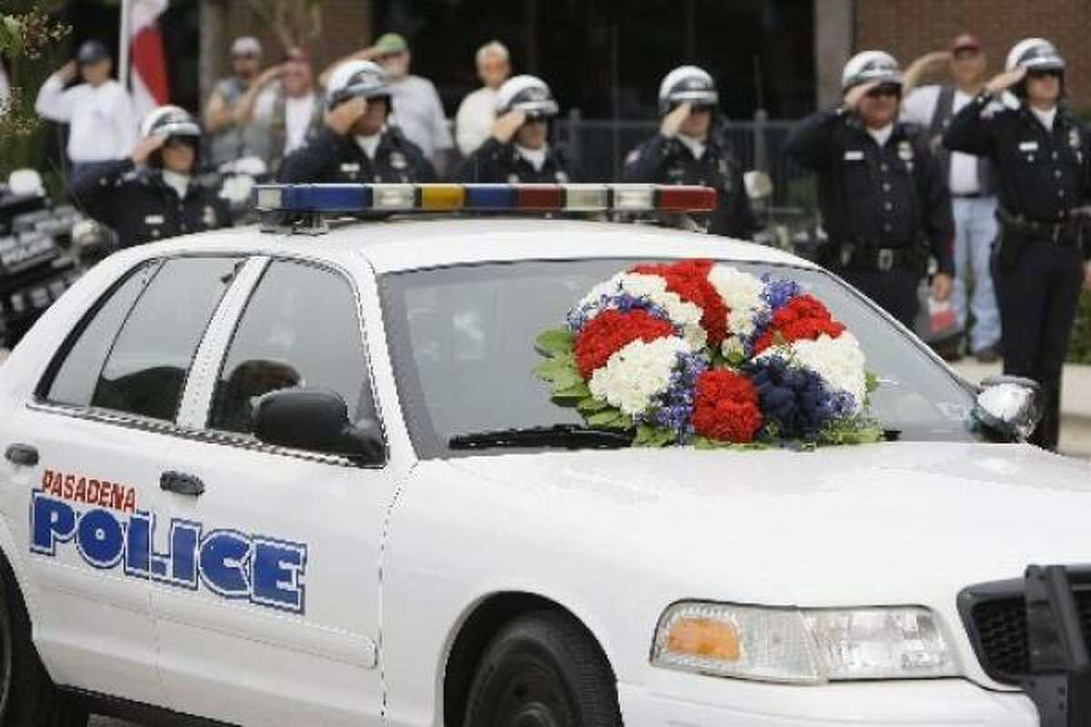 Flowers are placed on the patrol car of Pasadena Police Officer Jesse Hamilton during his funeral service.