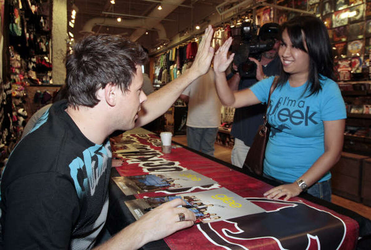 Cory Monteith gives a fan a high five as he signs autographs.