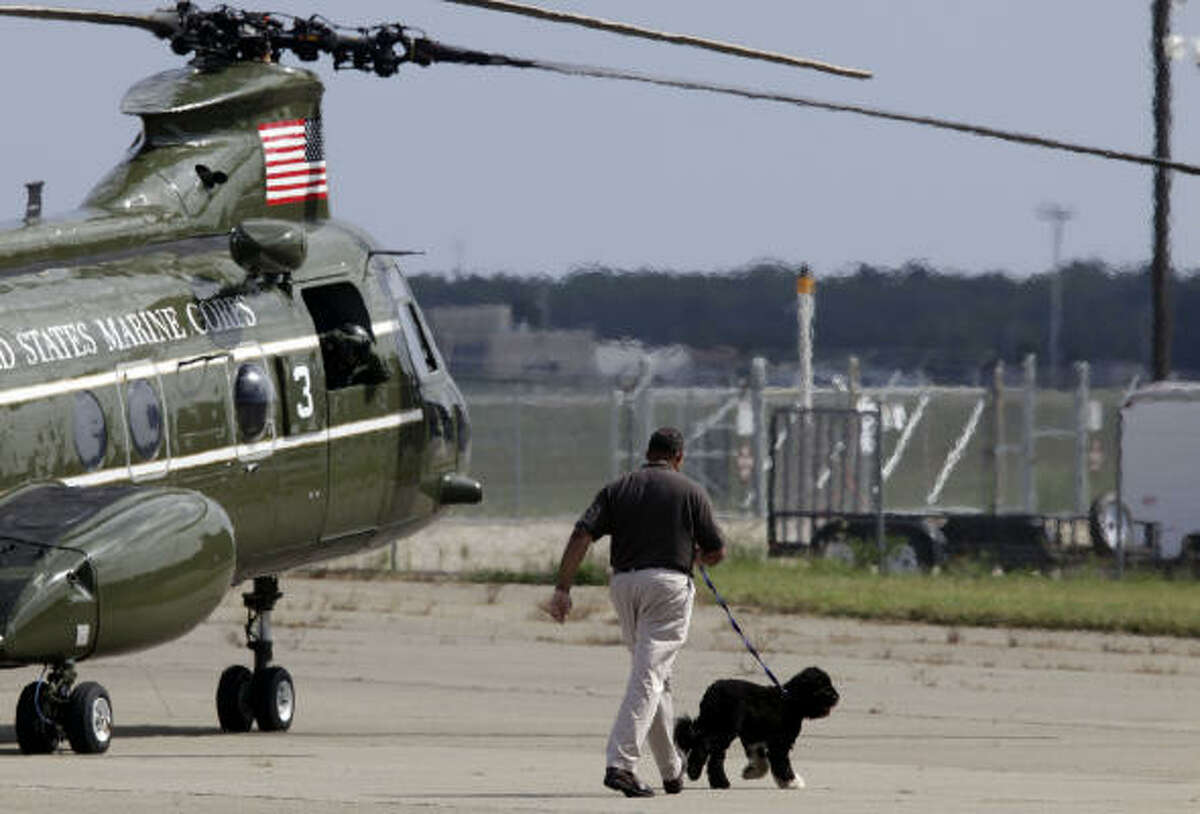 Bo is walked to the grass by his handler before boarding the helicopters in Cape Cod Coast Guard Air Station, Mass.