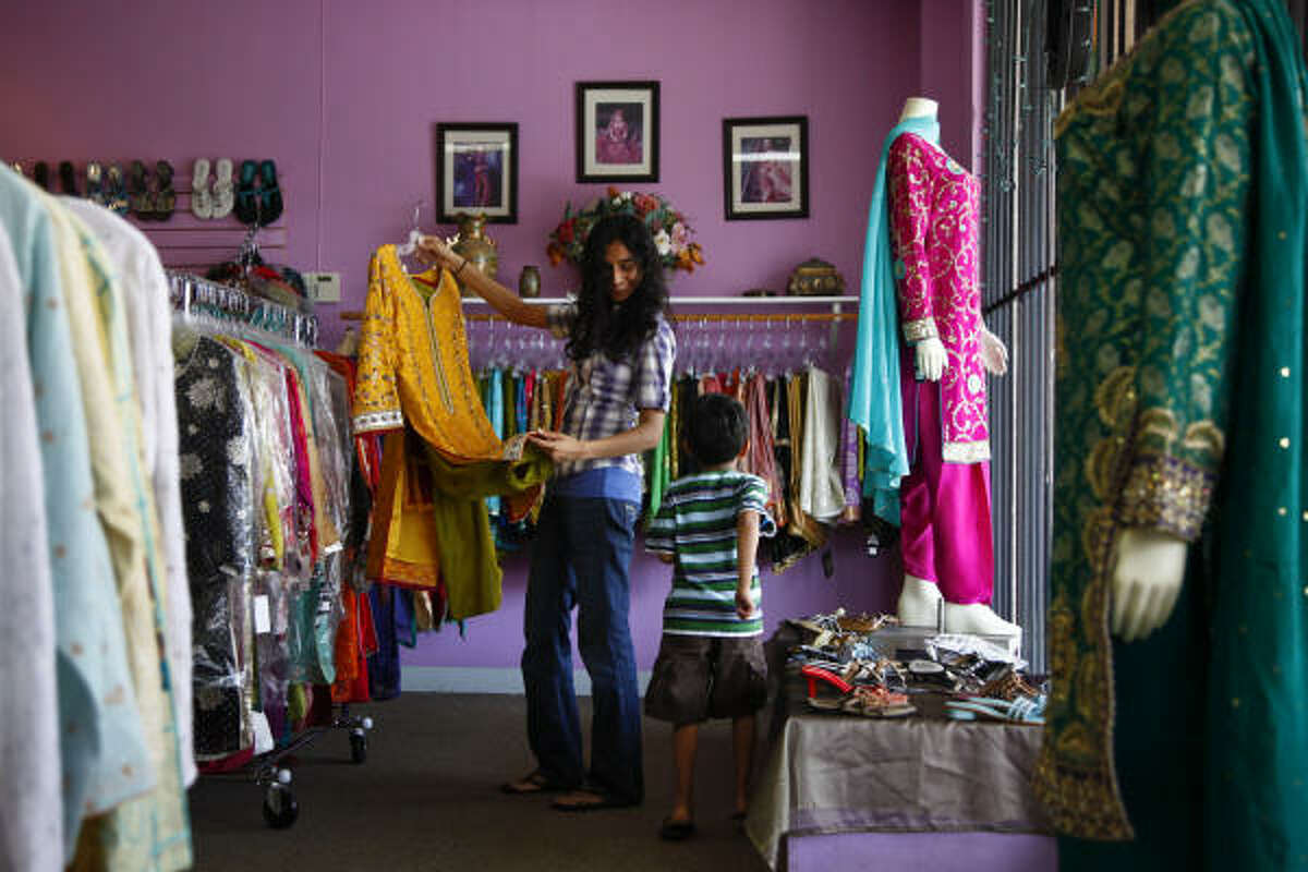 14-year-old Maha Khalid browses through a selection of salwar kameez at Bridals N More while her little brother Emad, 5, runs around. Many Muslims celebrate the end of Ramadan with new clothing such as the brightly colored, loose fitting salwar kameez garments.