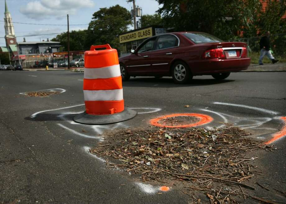 A traffic cone marks a hazardous section of roadway on State Street near Iranistan Avenue on Bridgeport's West Side on Thursday, October 8, 2009. Photo: Brian A. Pounds / Connecticut Post