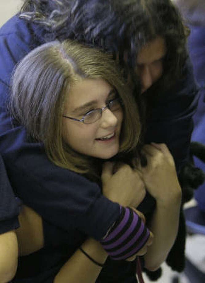 Alexus Rodgers, 14, sitting, is hugged by Laura Villeda, 13,  at the opening of classes at Fonville Middle School. Photo: Melissa Phillip, Chronicle