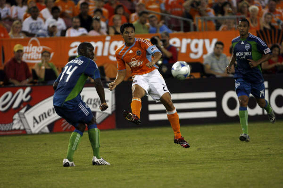 Aug. 23: Dynamo 1, Sounders FC 1 The Dynamo's Brian Ching, center, plays the ball past Seattle's Jhon Kennedy Hurtado.