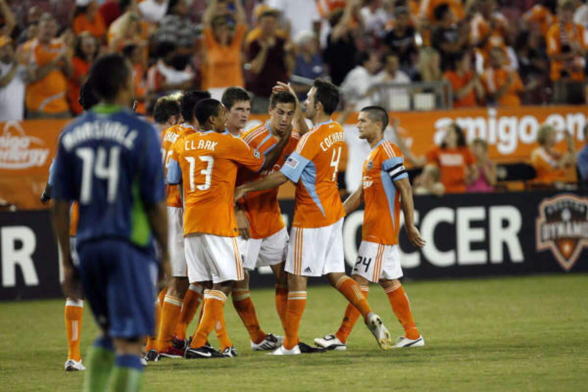 Dynamo players hug Geoff Cameron after Cameron scored the first goal of the game making it 1-0 in the first half.