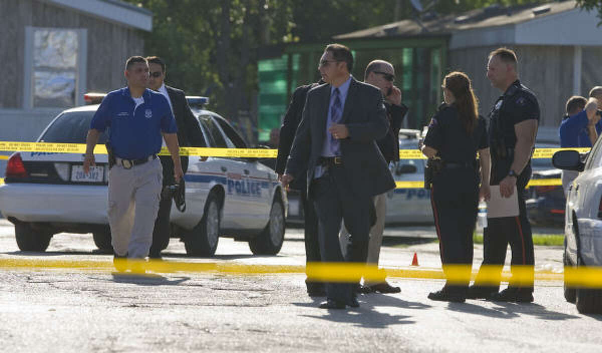 Pasadena police investigators work at the scene of a shooting in which an officer and suspect were shot Friday.