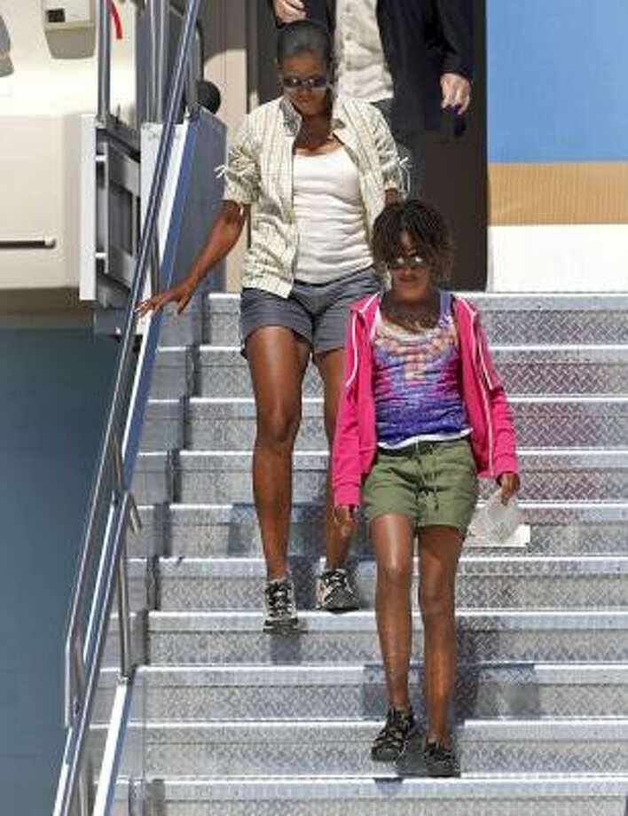Are shorts an inappropriate fashion choice for the first lady?  Michelle Obama walks down the stairs of Air Force One with her daughter Malia on a trip to the Grand Canyon recently. Photo: Matt York, AP