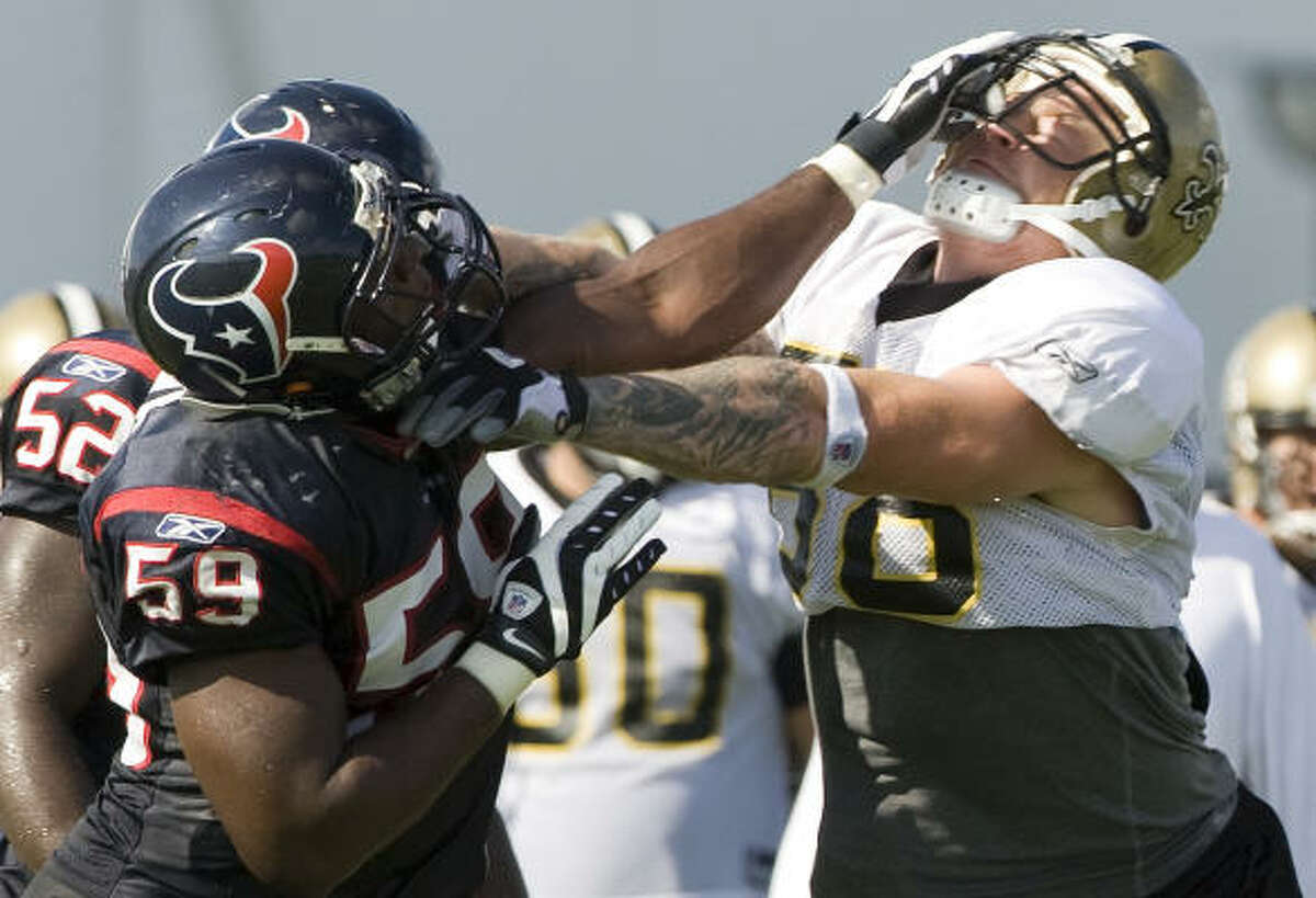 Texans linebacker DeMeco Ryans, left, and New Orleans Saints tight end Jeremy Shockey go at it during Thursday's practice.