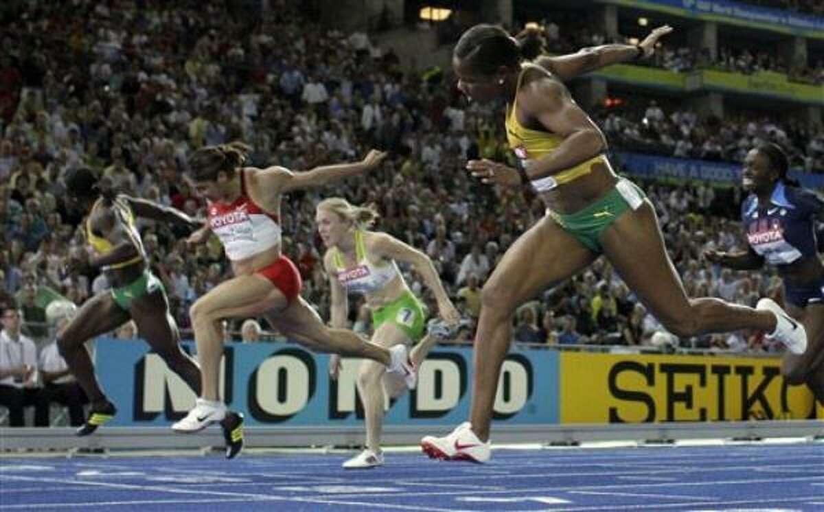 La jamaiquina Brigitte Foster-Hylton, derecha, cruza la meta para ganar los 100 metros con vallas en el mundial de atletismo el miércoles, 19 de agosto de 2009, en Berlín.