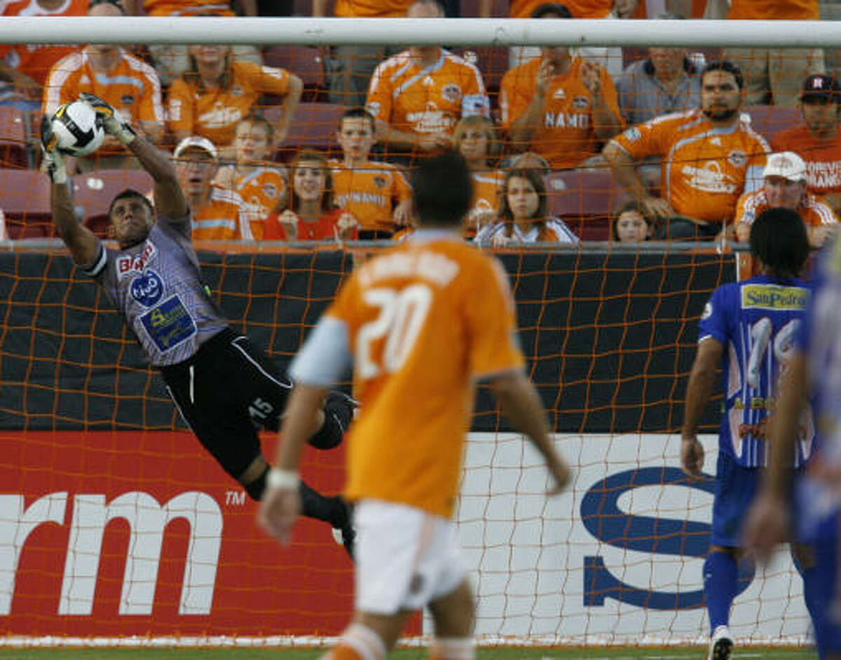 A.D. Isidro Metapan goalkeeper Alvaro Misael Alfaro makes a leaping attempt to stop a header by Dynamo forward Dominic Oduro.