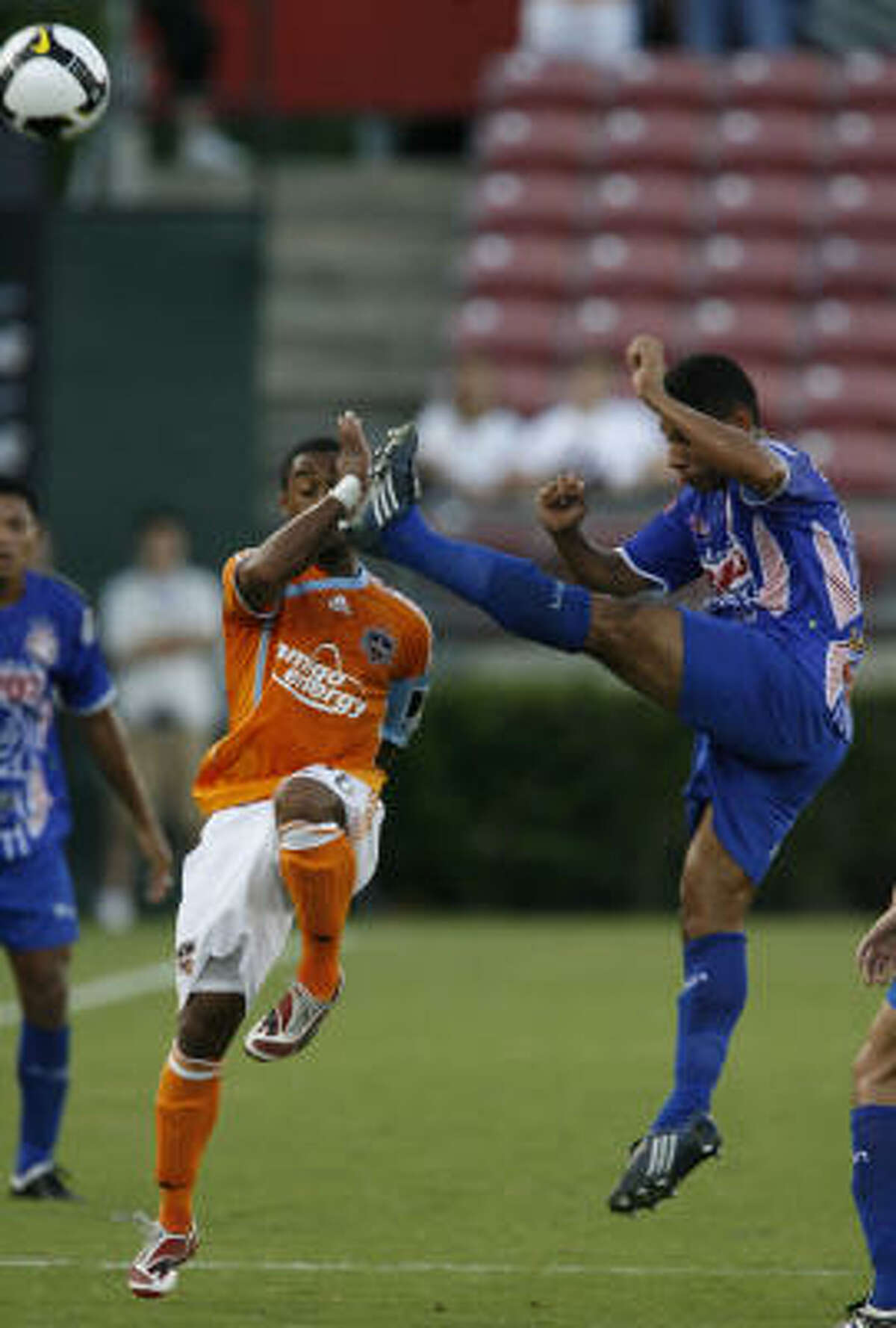 A.D. Isidro Metapan's Mario Edgardo Aguilar, right, gets his foot high near the head of Dynamo midfielder Corey Ashe.