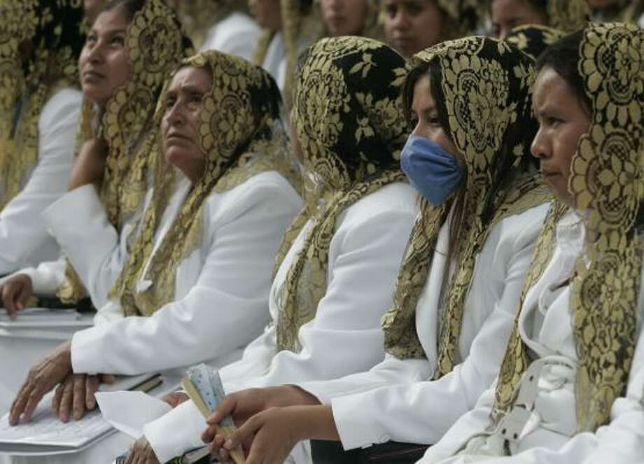 Worshipers, wearing traditional embroidered head veils, wait for Dr. Samuel Joaquin Flores, leader of the church. Post your photos of faith | HoustonBelief.com Photo: Carlos Jasso, AP