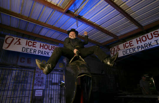 "Gator Conley rides the mechanical bull that was featured in the film ""Urban Cowboy."" In 1980, Conley was teaching John Travolta how to ride the bull; now it sits in the shuttered G's icehouse in Deer Park. Photo: Karen Warren, Houston Chronicle"