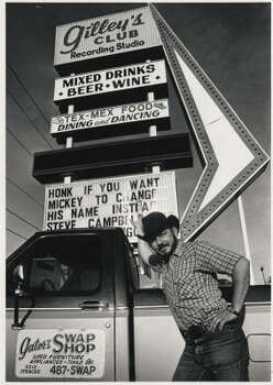 Gilleyrat Gator Conley stands next to the sign at Gilley's Club in 1980 for the 25th Anniversary of the movie Urban Cowboy. Photo: Houston Chronicle File
