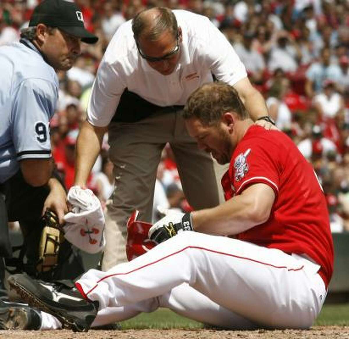 Cincinnati Reds' Scott Rolen, right, looks at his helmet as he checked out by Reds trainer Mark Mann,.