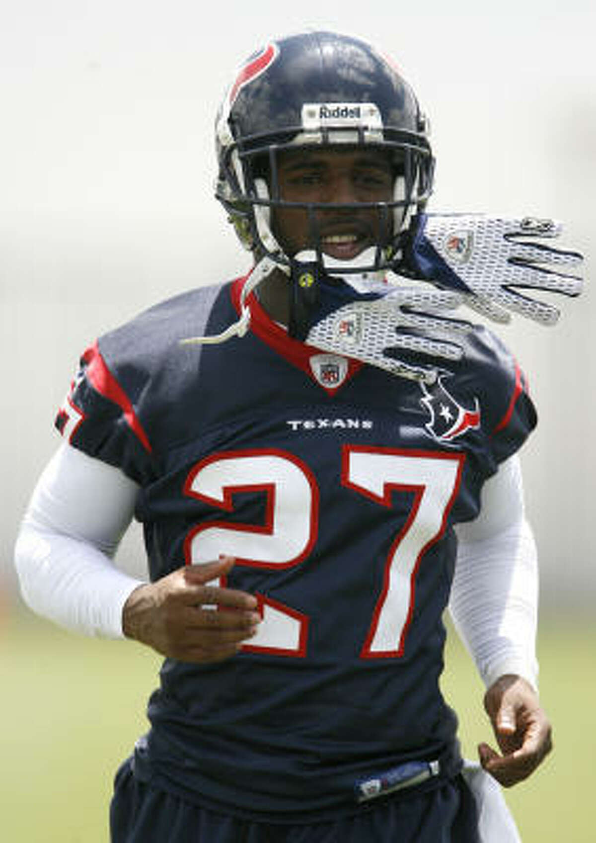 Texans corner back Matterral Richardson runs with his gloves attached to his helmet during the afternoon practice session.