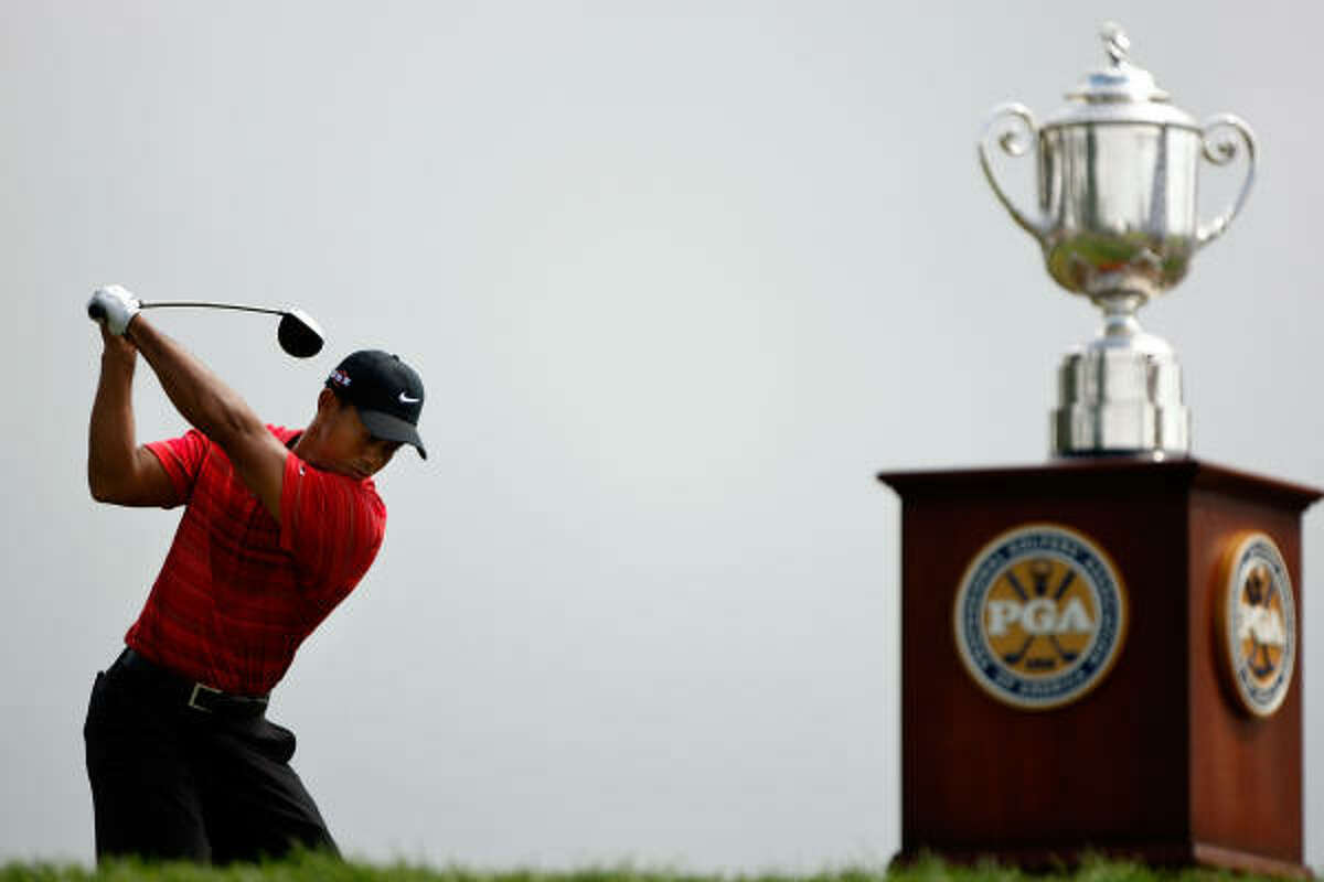Tiger Woods hits his tee shot alongside the Wanamaker Trophy on the first hole.
